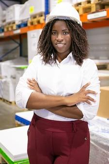 Gelukkige zwarte vrouwelijke bedrijfsdame die veiligheidshelm draagt, die zich met gekruiste wapens bevindt en in magazijn stelt. verticaal schot. arbeids- en inspectieconcept