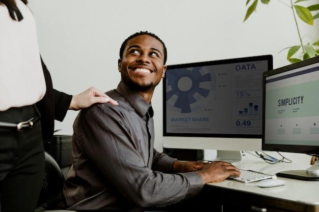 Gelukkige zwarte zakenman die aan een computerschermmodel werkt