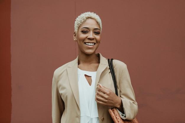 Gelukkige zwarte zakenvrouw die door de straten slentert