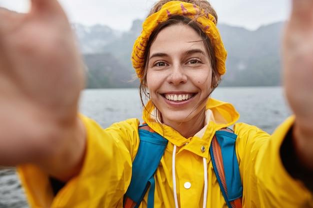 Gelukkige zwerver geniet van avontuurlijke reis, maakt selfie tegen majestueus berglandschap