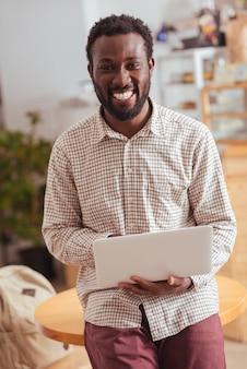 Gelukkigste werknemer. vrolijke jonge man zittend op de tafel in koffiehuis, met een laptop en vrolijk lacht naar de camera