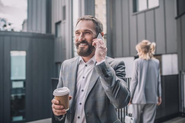Geluksdag. zakelijke gelukkig volwassen man in stijlvol grijs pak met koffie praten over smartphone en vrouw met rug in de verte