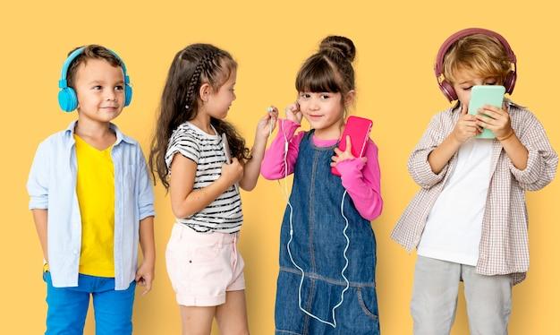 Geluksgroep van schattige en schattige kinderen die naar muziek luisteren