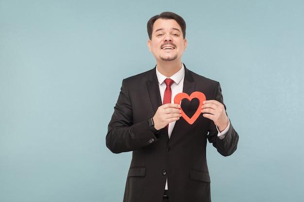 Geluksman die een klein rood hart vasthoudt en naar de camera kijkt