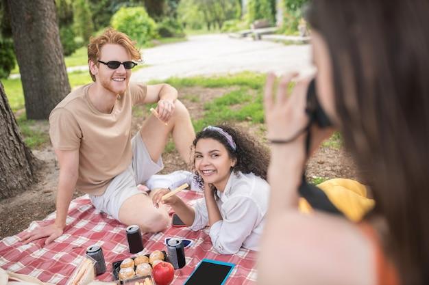 Geluksmomentje. jong meisje dat foto's maakt van lachende, ontspannen vrienden die op een warme dag op picknick rusten
