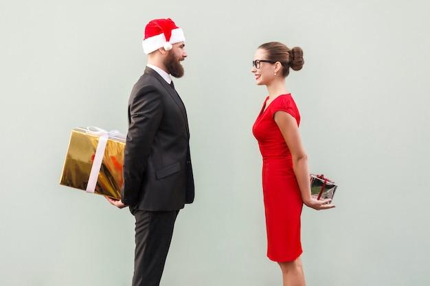 Gelukspaar dat naar elkaar kijkt en een geschenkdoos achter de rug houdt. studio opname
