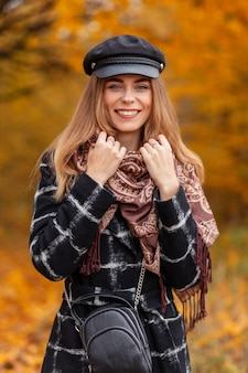 Geluksportret van een mooie glimlachende vrouw met hoed en vintage sjaal in modejas met handtas geniet van en wandelt door de natuur met gele herfstbladeren