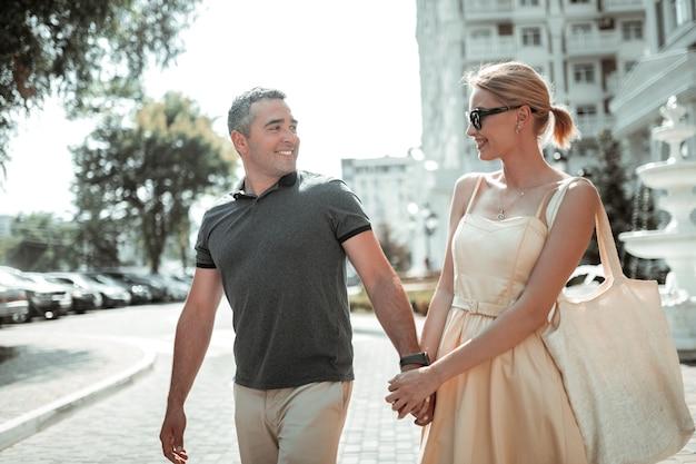 Geluksvogel. gelukkig lachende man die naar zijn mooie vrolijke vrouw kijkt en haar hand vasthoudt terwijl ze door de stad loopt.