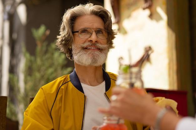 Geluksvogel. vrolijke bebaarde man die zich gelukkig voelt door smoothie te drinken tijdens de lunch met zijn vrouw in het straatcafé.