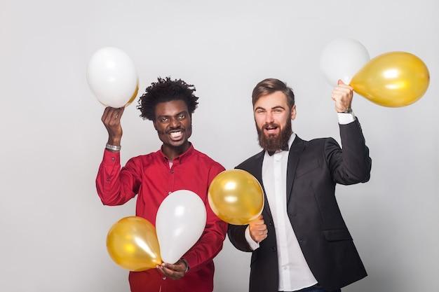 Geluksvrienden die verjaardag vieren, gouden en witte luchtballon vasthouden, handen omhoog en glimlachen. studio opname, grijze muur