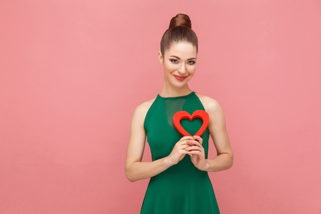 Geluksvrouw die rood hart houdt en glimlacht