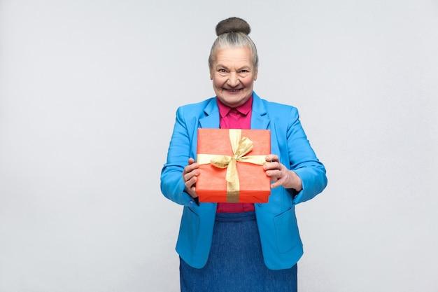 Geluksvrouw met rode geschenkdoos en brede glimlach