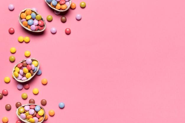 Gem-snoepjes in de gebroken chocoladepaaseieren op roze achtergrond