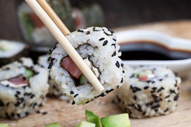 Gemaakt van rijst en forel of zalm met groenten sushi eten, aziatische rijst en zeevruchten op tafel tijdens maaltijden, aziatische etenswaren
