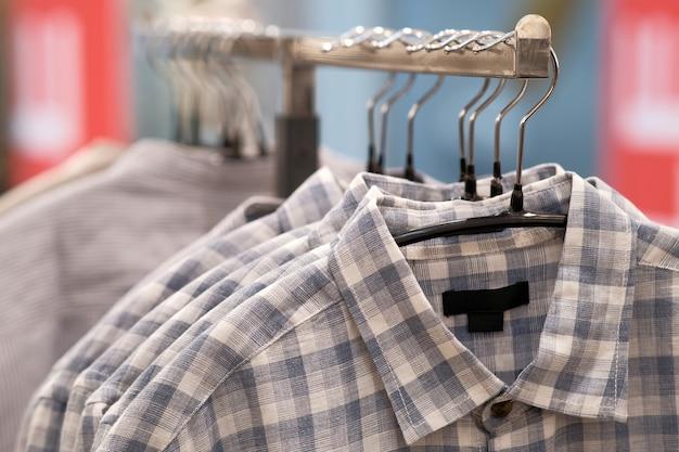 Gemaakte rustieke linnen kleding hangt aan hangers in de winkel.