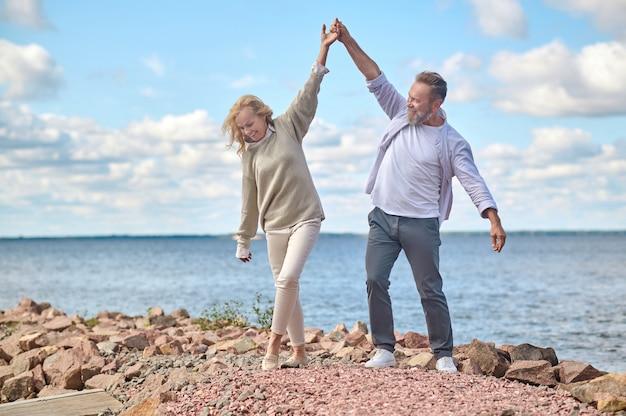 Gemak. vrolijke volwassen man en vrouw hand in hand in lichte dansbeweging met vrije tijd in de buurt van zee