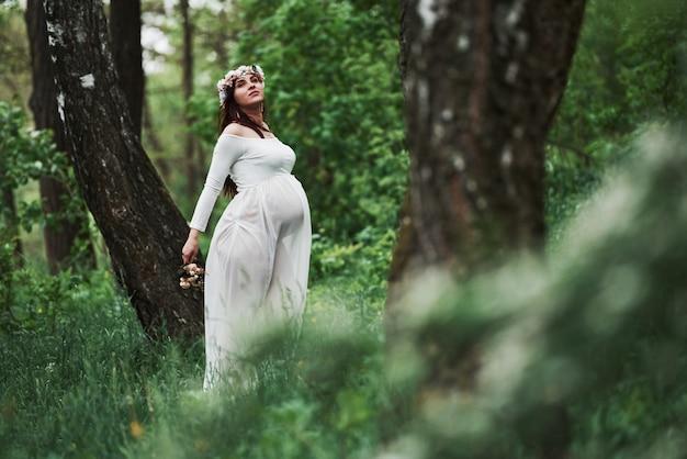 Gemakkelijke wind die door het bos gaat. mooie zwangere vrouw in jurk wandelen buiten. positieve brunette