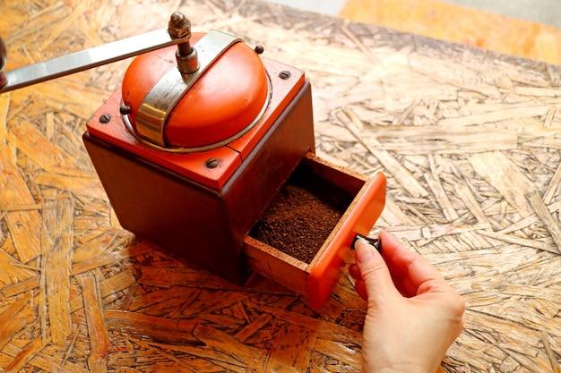Gemalen koffie in de levendige oranje kleur retro koffiemolen klaar voor zelfgemaakte koffie
