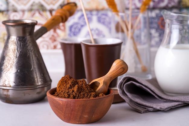 Gemalen koffie in een houten kom met bruine suikerstok