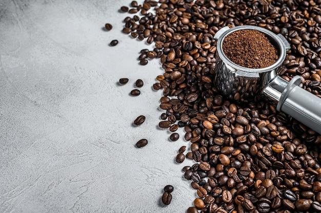 Gemalen koffie in filterhouder voor espresso met koffiebonen.