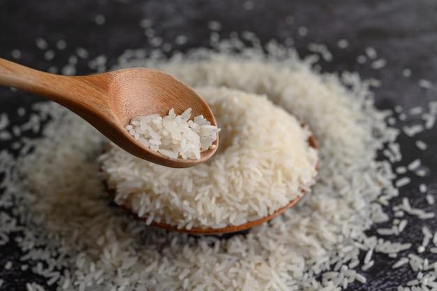 Gemalen rijst in een kom en een houten lepel op de zwarte cementvloer.