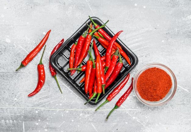 Gemalen rode peper in een kom en de paprika's op het dienblad op rustieke tafel.