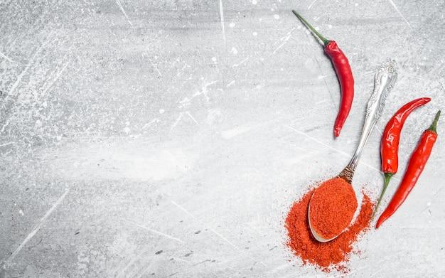 Gemalen rode peper in een lepel met verse peperpeulen op rustieke lijst.