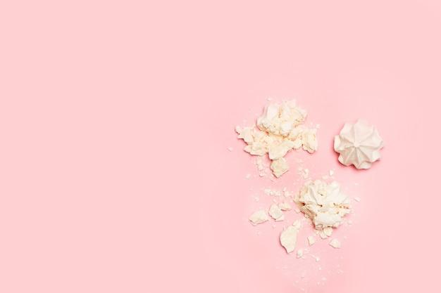Gemalen schuimgebak op een roze achtergrond in een bovenaanzicht met kopie ruimte