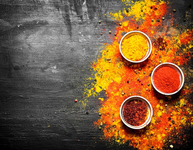 Gemalen specerijen en kruiden uit india. op het zwarte bord.