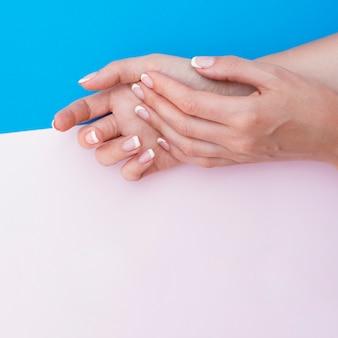 Gemanicuurde handen met roze kopie ruimte