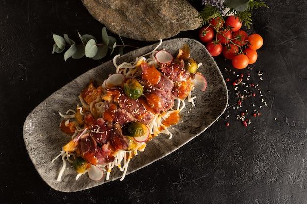 Gemarineerd rundvlees op een bedje van gestoofde groenten, spruitjes en radijsjes. rundvlees hoofdgerecht met groentegarnituur