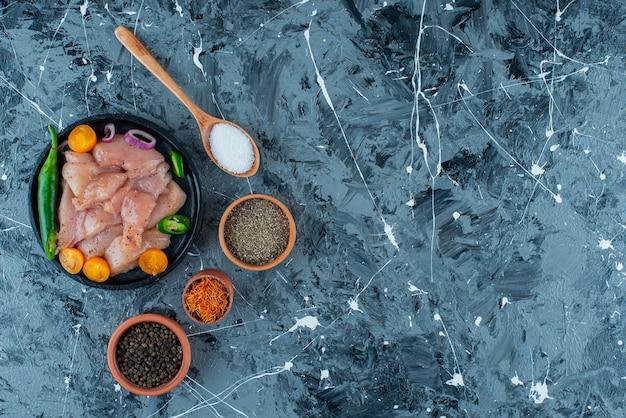 Gemarineerd vlees en groenten op een plaat naast kruiden in kommen en lepel, op de blauwe achtergrond.
