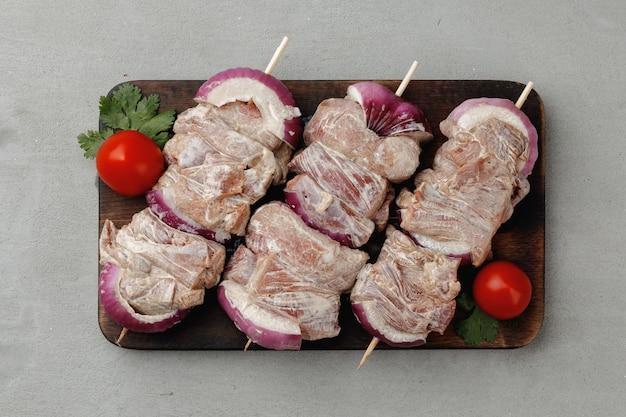Gemarineerd vlees op spiesjes met ui op grijze tafel