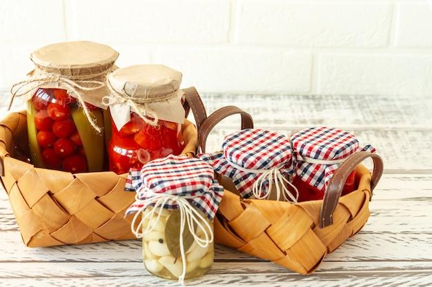 Gemarineerde augurken inmaakpotten. huisgemaakte tomaten, komkommers, knoflook, gember en mierikswortel augurken. gefermenteerd voedsel.