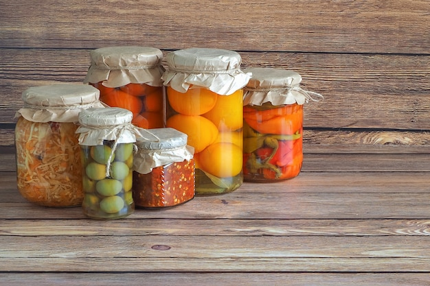 Gemarineerde augurken variëteit conservenpotten op de houten keukentafel. gefermenteerde zelfgemaakte gerechten.