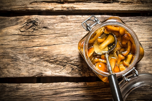 Gemarineerde champignons in de pot op houten tafel.