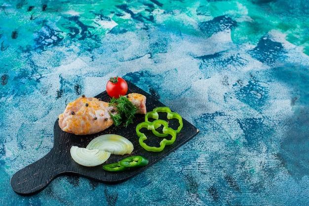 Gemarineerde drumstick en gesneden groenten op een snijplank, op de blauwe achtergrond.