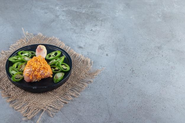 Gemarineerde drumstick en gesneden peper op een bord op het jute servet, op de marmeren achtergrond.
