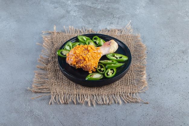 Gemarineerde drumstick en gesneden peper op een bord op het jute servet, op het marmeren oppervlak.