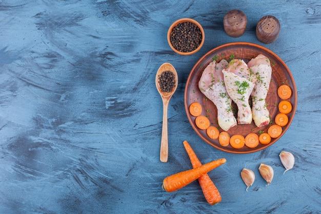 Gemarineerde drumsticks en gesneden wortelen op een houten plaat naast kruiden, lepel en knoflook, op de blauwe achtergrond.