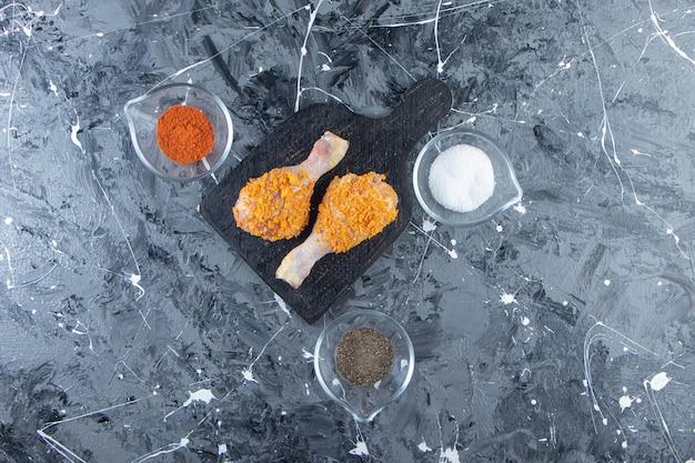 Gemarineerde drumsticks op een snijplank naast kruidenkommen, op het marmeren oppervlak.