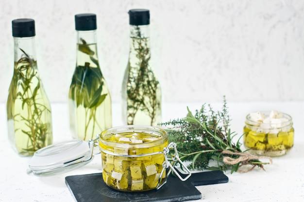 Gemarineerde feta in een glazen pot, specerijen en gearomatiseerde olijfolie op een houten achtergrond