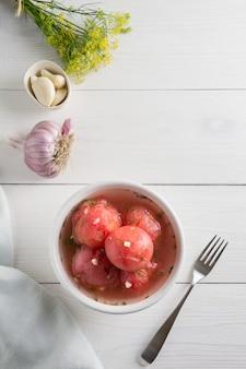 Gemarineerde gepelde tomaten met knoflook en dille, vers klaar om te serveren.