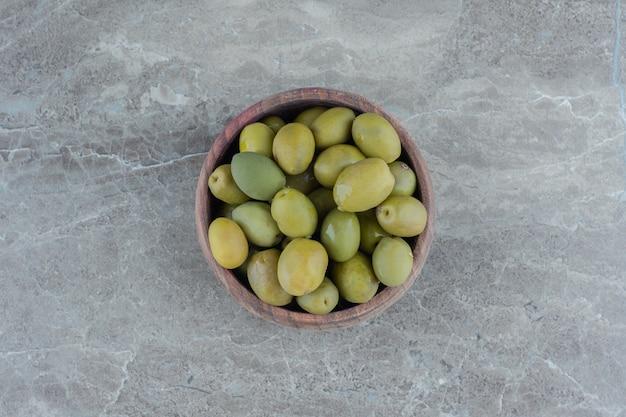 Gemarineerde groene olijven. stapel groene olijven in houten kom.