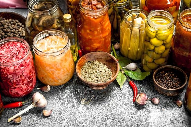 Gemarineerde groenten met kruiden in glazen potten