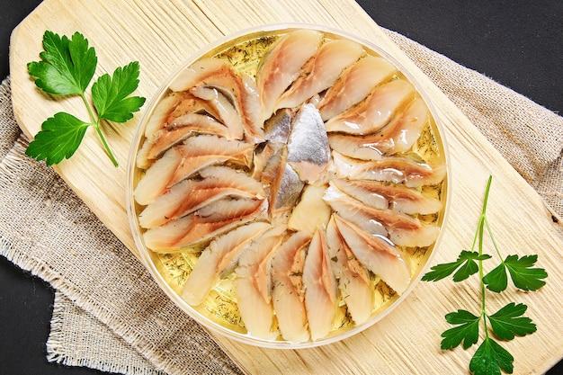 Gemarineerde haring in olie op een houten bord op een grijze donkere tafel. tussendoortje.
