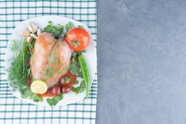 Gemarineerde hele kip op bord met groenten.