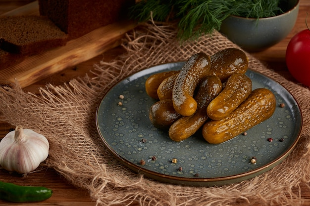 Gemarineerde ingelegde komkommers in plaat met kruiden op houten