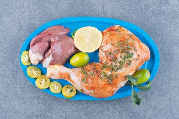 Gemarineerde kip en vlees op blauw bord.