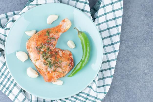 Gemarineerde kip met knoflook en peper op blauw bord.